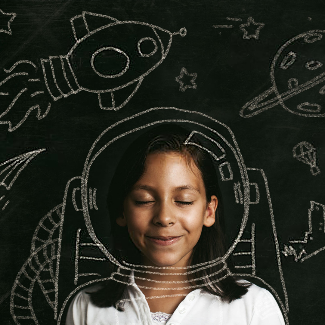 A brown skinned girl school girl, closes her eyes an dreams of becoming a scientist, an astronaut, changing the world